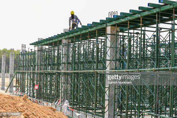 construction workers are installation scaffolding for support structure building second beam and second floor at construction site - fabricage apparatuur stock pictures, royalty-free photos & images