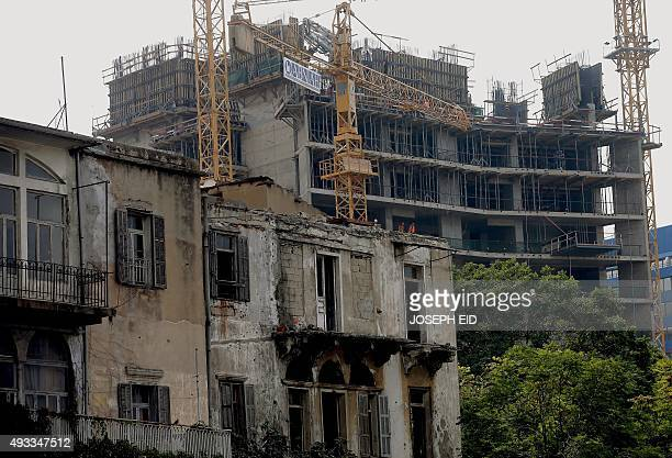Construction workers are seen at a construction site behind an old building in Beirut on October 19 2015 Conservationists are rushing to save what is...