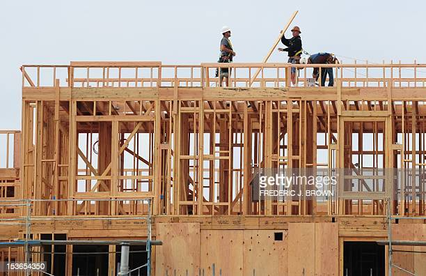 Construction workers are seen atop a builing of new apartments for sale in Alhambra east of downtown Los Angeles on March 23 2012 in California Sales...