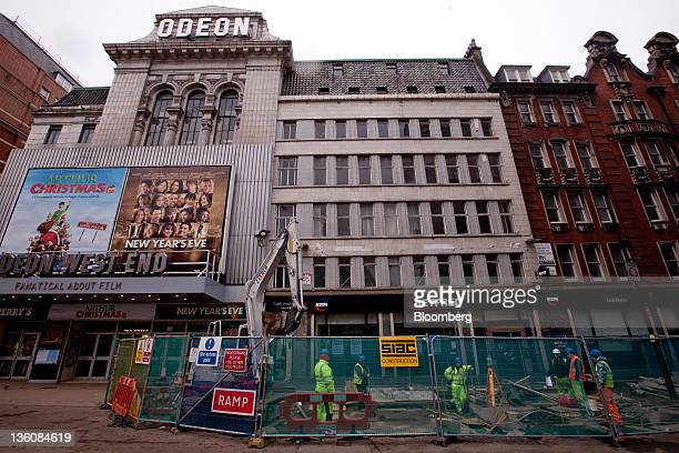 Construction workers are seen outside an Odeon cinema on Leicester Square in central London UK on Monday Dec 19 2011 A site on Leicester Square in...
