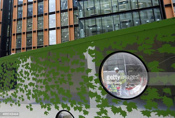 Construction workers are seen through a viewing aperture in construction hoardings as they work on the Three Pancras Square development in the King's...