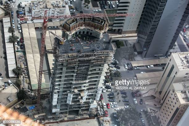 Construction workers assemble steel meshes at the site of a tower under construction in the downtown district of Kuwait City on February 21 2018 /...