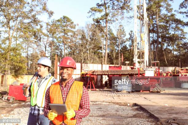 Construction workers at outdoor drilling site.