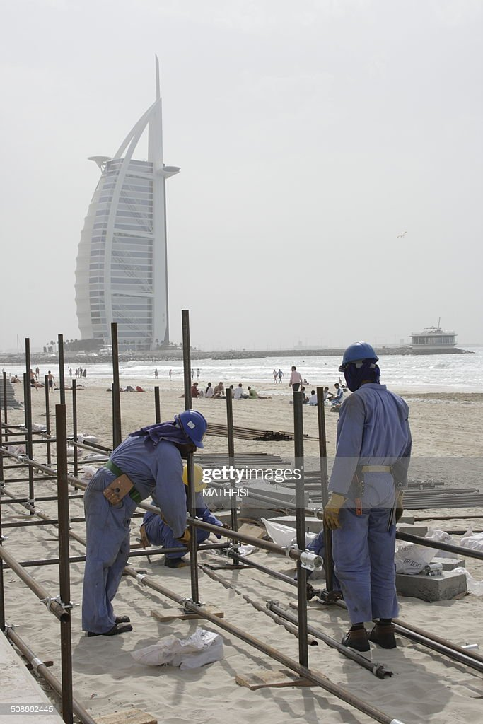 Construction Workers at the beach in Front of Burj al Arab Hotel, Dubai, United Arab Emirates