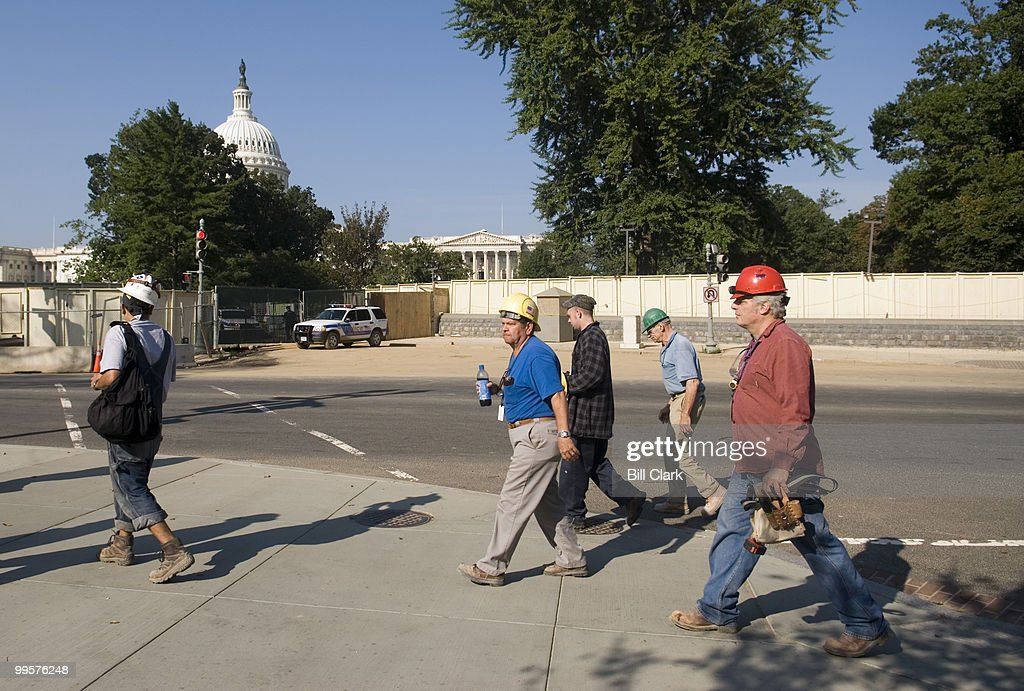 Construction workers at the Capitol Visitors Center head back to work after a man drove his SUV through the gates leading to the construction site on the east side of the Capitol on Monday morning, Sept. 18, 2006. After the driver crashed his car into a fountain on the plaza, he ran into the Capitol building where he was arrested by police.