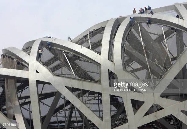 Construction workers atop the 2008 Olympics National Stadium in Beijing, also known as the Bird's Nest for its architectural design, 11 October 2007....