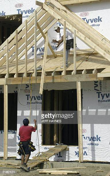 Construction workers build a new home 21 July 2003 in Naperville IL a suburb of Chicago The index of leading US economic indicators rose 01 percent...