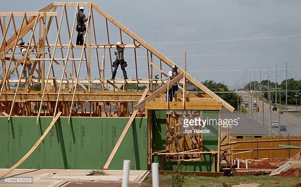 Construction workers build a new home to replace the one that was destroyed almost one year ago by a tornado on May 19 2014 in Moore Oklahoma On May...