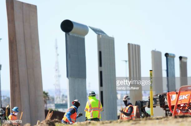 Construction workers build a secondary border wall with the prototype models in back on February 22 2019 in Otay Mesa California The Department of...