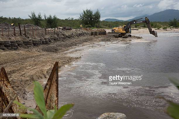 Construction workers build a small interim port inside the planned Dawei SEZ on August 3 2015 in Ngapitat MyanmarThe controversial multibillion...