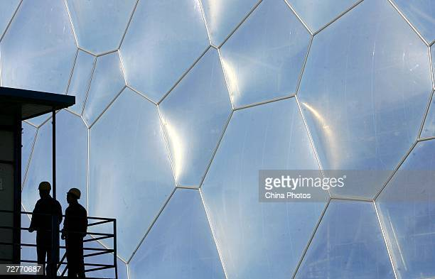 Construction workers build at the National Aquatics Center dubbed the Water Cube December 7 2006 in Beijing China Continuous progress has been made...
