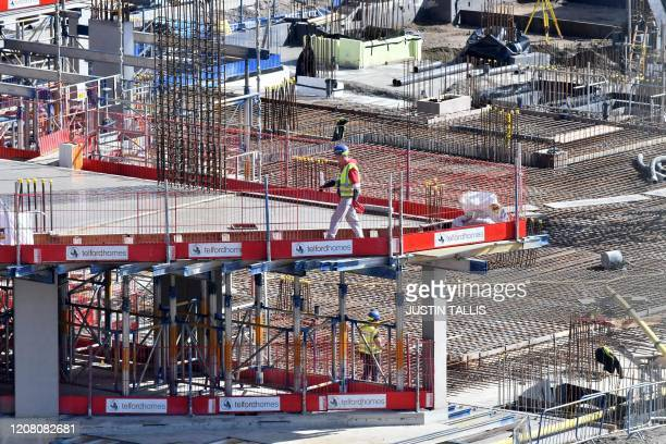 Construction workers build new apartments and retail complex at Nine Elms in south London on March 24 as Britain's Chancellor of the Duchy of...