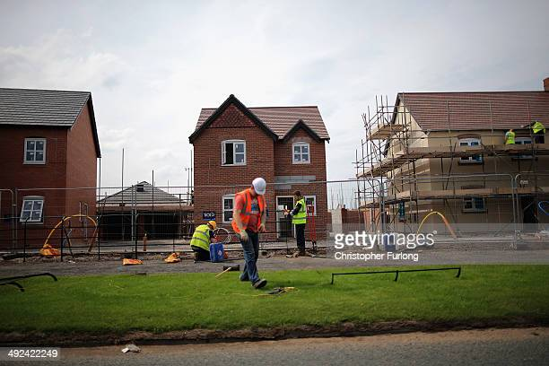Construction workers build new houses on a housing development on May 20 2014 in Middlewich England Official figures have shown that house prices...