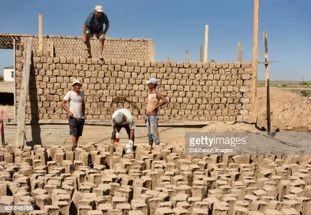 Construction workers building mud brick house in development outside Shymkent Kazakhstan
