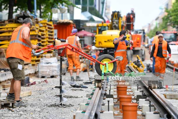 Construction workers busy working on the roadbed of the tram at the large construction site along the Planken shopping street in Mannheim Germany 02...