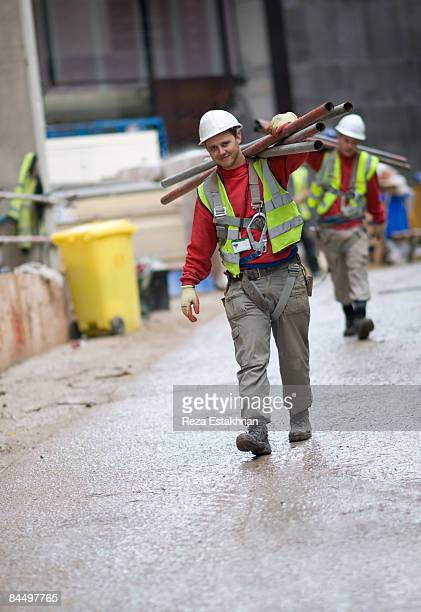 construction workers carry scaffolding - bauarbeiter stock-fotos und bilder
