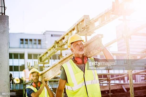 Construction workers carrying plank at site