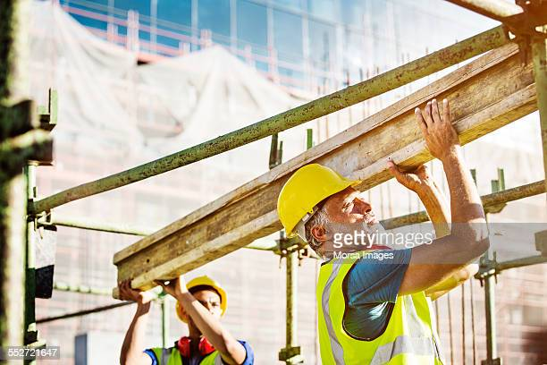 Construction workers carrying plank