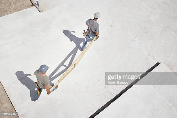 Construction workers carrying roof truss on construction site