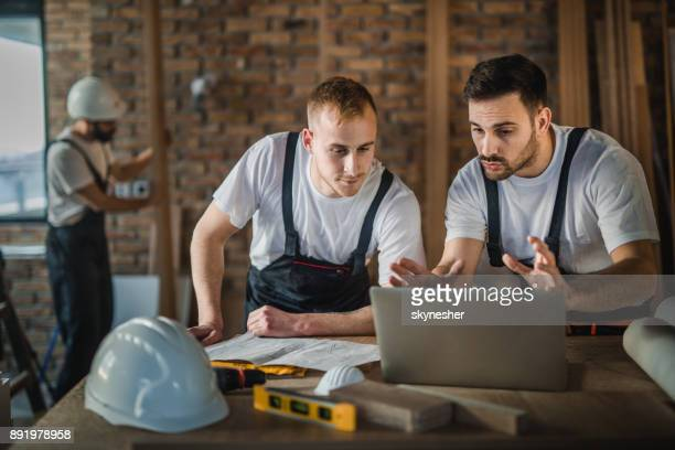 Construction workers cooperating while working on laptop during home renovation process.