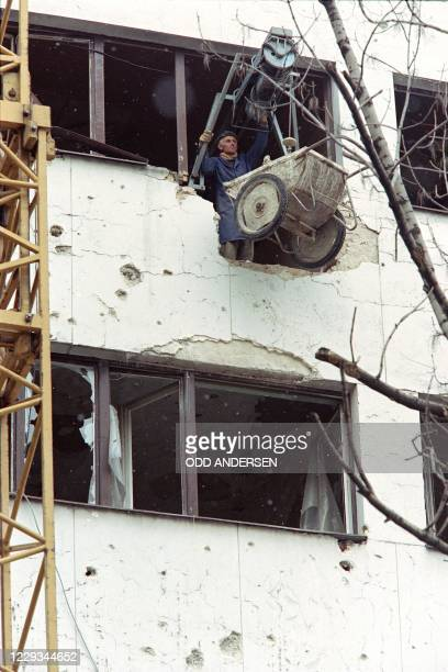 Construction workers crane material and equipment to a higher floor of a totally bombed-out office block on Sarajevo's Sniper Alley, on November 08,...