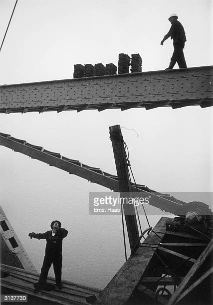 Construction workers crossing a girder during building work on the Golden Gate Bridge in San Francisco California