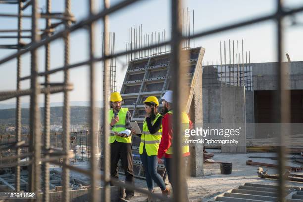 construction workers discuss the building plans. - built structure stock pictures, royalty-free photos & images