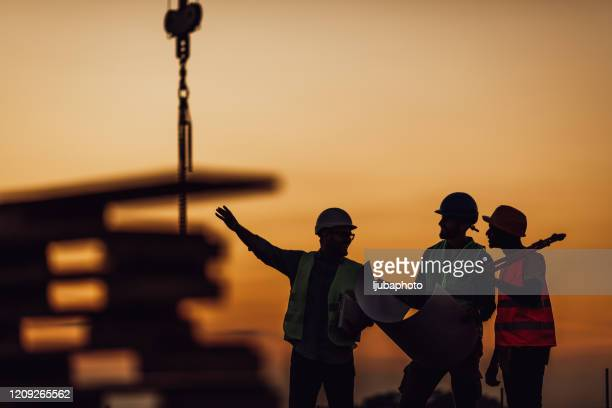 i lavoratori edili discutono i piani edilizi - industria edile foto e immagini stock