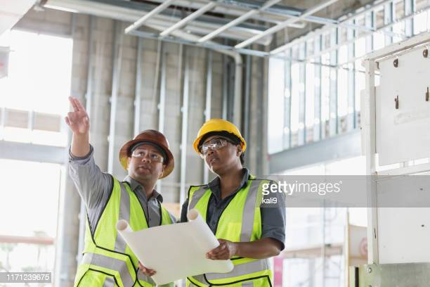 construction workers discussing floor plans - protective eyewear stock pictures, royalty-free photos & images