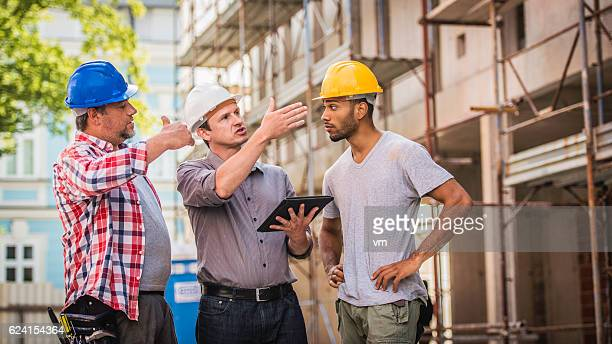 Construction workers discussing plans with foreman