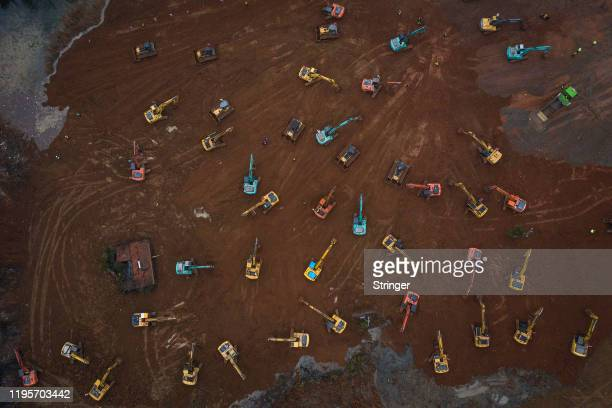 Construction workers drive excavators at the site of a new 1000bed field hospital being built to accommodate the increasing number of coronavirus...
