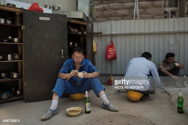 TOPSHOT Construction workers eat their lunch at a construction site in Beijing on July 13 2016 China's growth slipped to a new sevenyear low of 66...