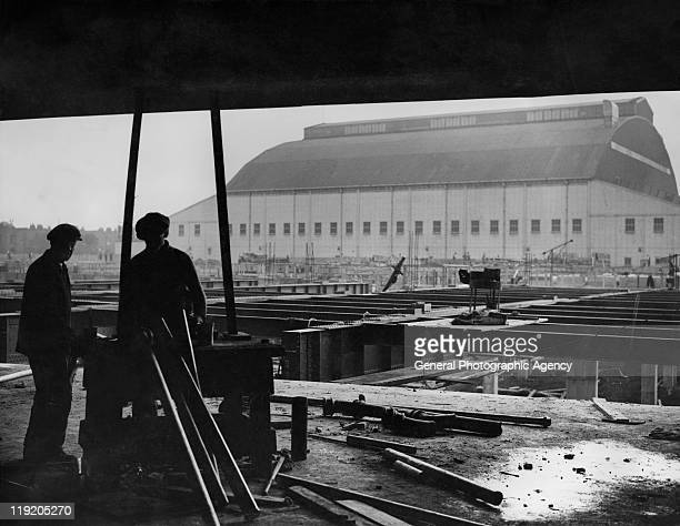 Construction workers erect a new bridge for traffic outside the Earls Court Exhibition Centre under construction in London circa 1935