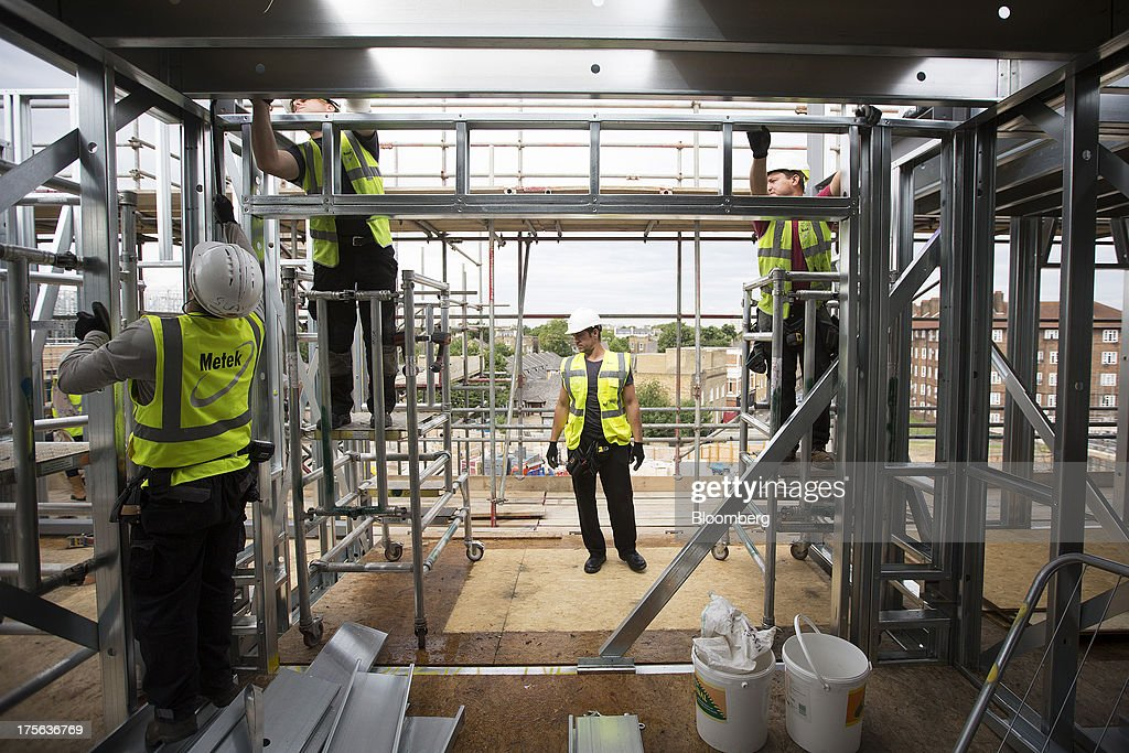Construction workers erect metal support frames at the Oval Quarter, a shared ownership, private and social residential housing complex developed by Higgins Group Plc in partnership with Nottinghill Housing and Pinnacle Regeneration Group, in London, U.K., on Monday, Aug. 5, 2013. U.K. house prices rose 0.8 percent in July, from 0.3 percent the previous month, Nationwide Building Society said. Photographer: Simon Dawson/Bloomberg via Getty Images