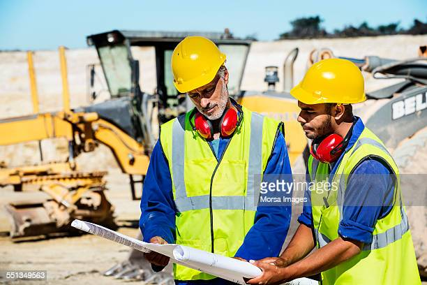Construction workers examining blueprint at quarry