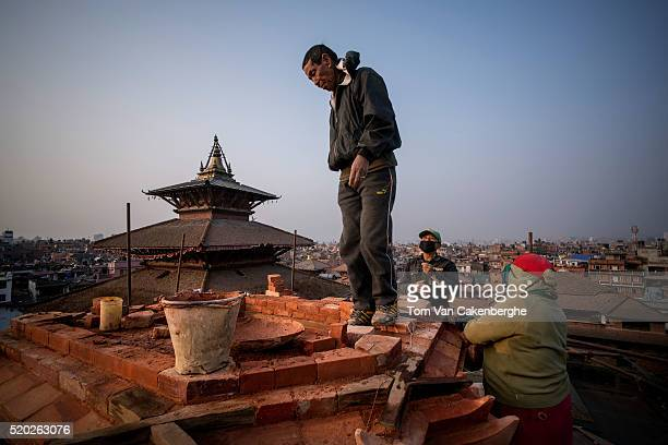 Construction workers experienced in traditional Nepali style architecture are standing on a scaffold and rebuild the top of the major Taleju temple...