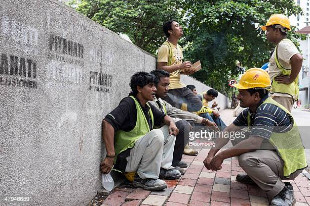 Construction workers from Bangladesh take a break in Kuala Lumpur, Malaysia, on Tuesday, March 18, 2014. Malaysia, aspiring to become a developed...