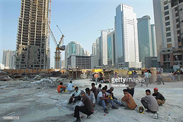 Construction workers from Bangladesh take a break near new highrise office buildings and hotels still under construction in the new City Center and...
