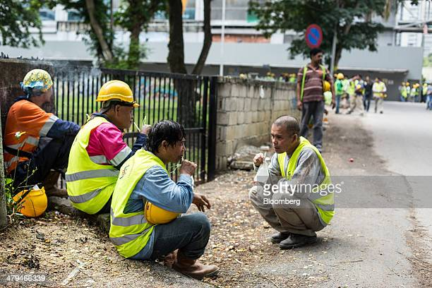 Construction workers from the Philippines take a break in Kuala Lumpur, Malaysia, on Tuesday, March 18, 2014. Malaysia, aspiring to become a...