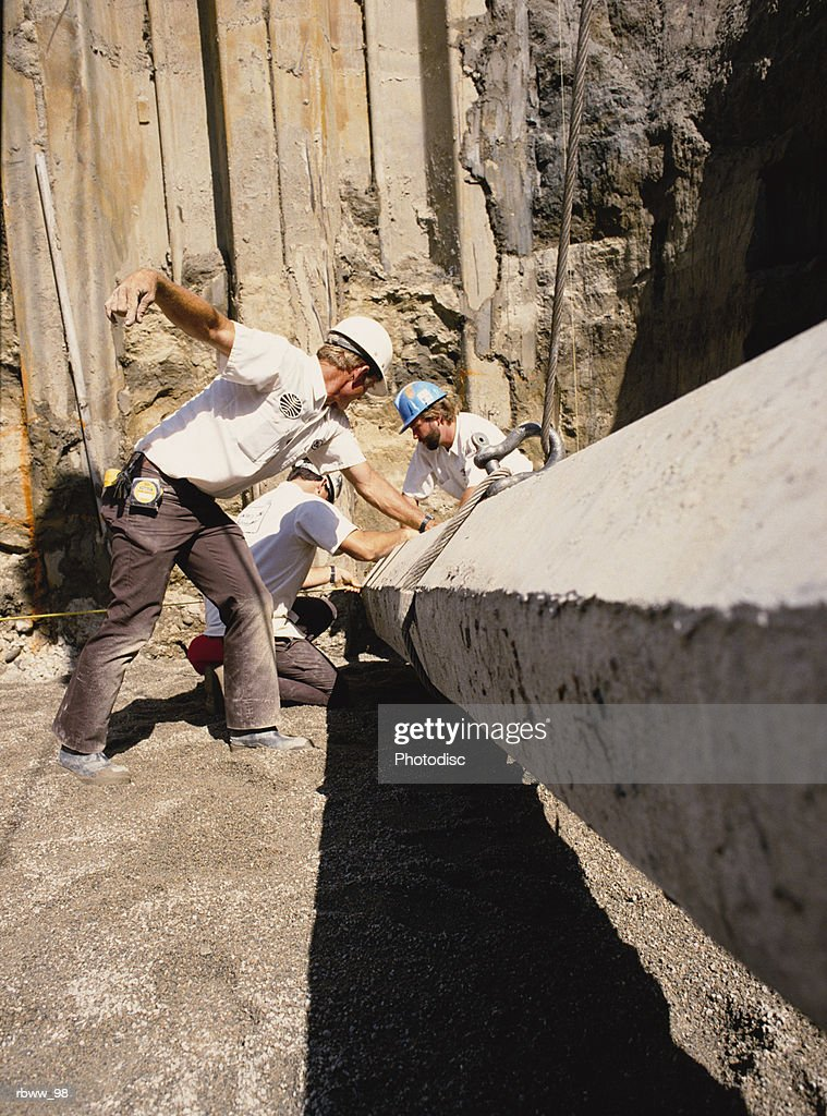construction workers gather around a concrete beam : Foto de stock