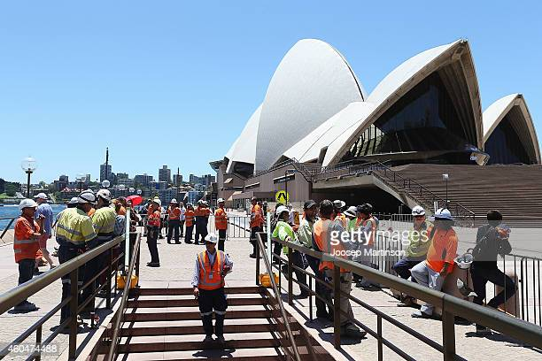 Construction workers gather in front of the Sydney Opera House after being evacuated on December 15, 2014 in Sydney, Australia. Major landmarks in...