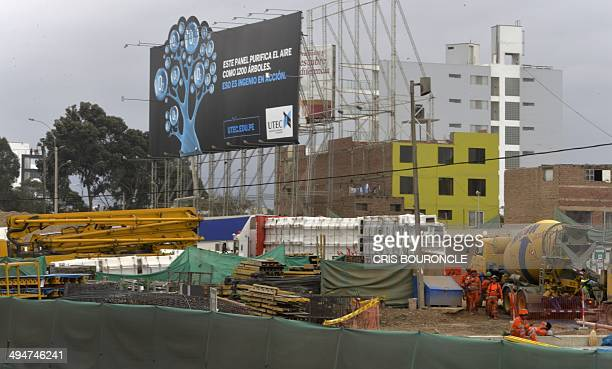 Construction workers go about their chores at a site in Lima on May 30 2014 near a billboard that filters pollution from the air and is capable of...