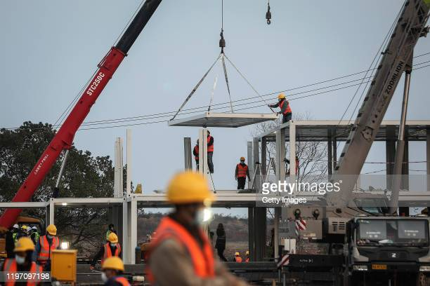 Construction workers guide a crane as new hospitals are built to tackle the coronavirus on January 28 2020 in Wuhan China Wuhan Huoshenshan hospital...