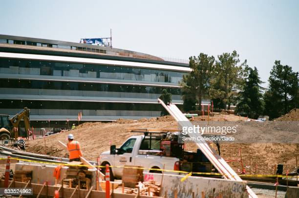 Construction workers handle lumber with other workers visible on the roof of the main building at the Apple Park known colloquially as 'The...