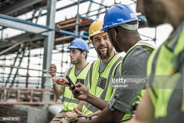 construction workers having a break on construction site - lunch break stock pictures, royalty-free photos & images