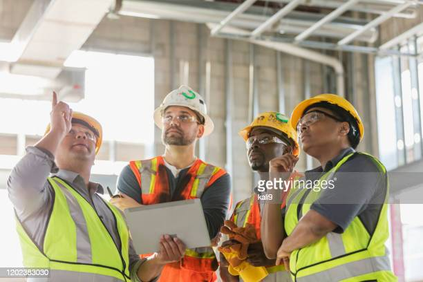construction workers having meeting, with digital tablet - foreperson stock pictures, royalty-free photos & images