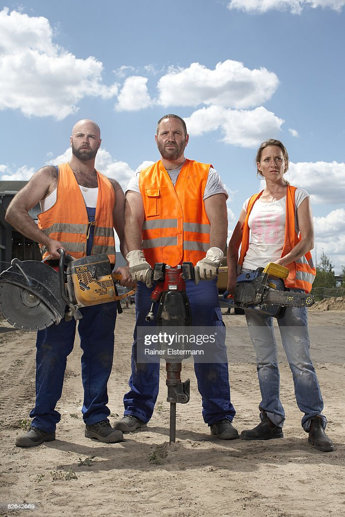 3 construction workers holding machinery : Stock Photo
