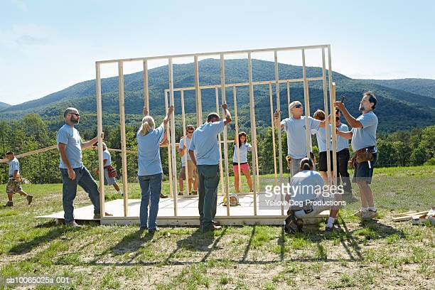 Construction workers holding wooden frame of house