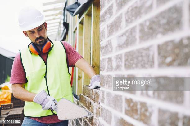 construction workers in australian in building site working and doing tasks. - one man only stock pictures, royalty-free photos & images