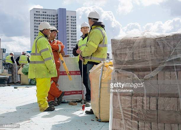 construction workers in discussion - newpremiumuk stock pictures, royalty-free photos & images